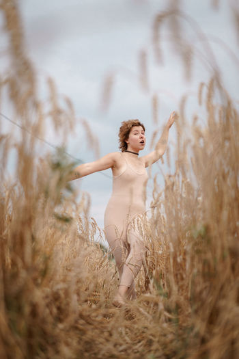 Woman with arms raised standing on field