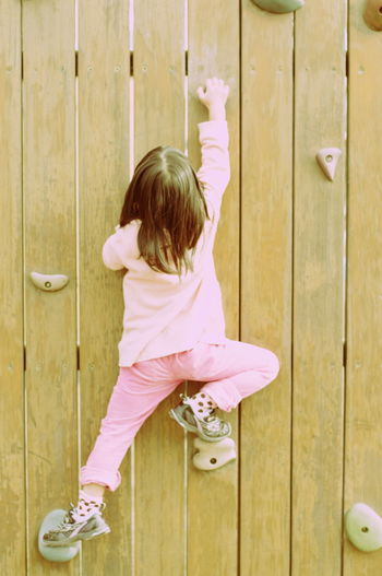Rear View Of Girl Practicing Rock Climbing On Wood Wall