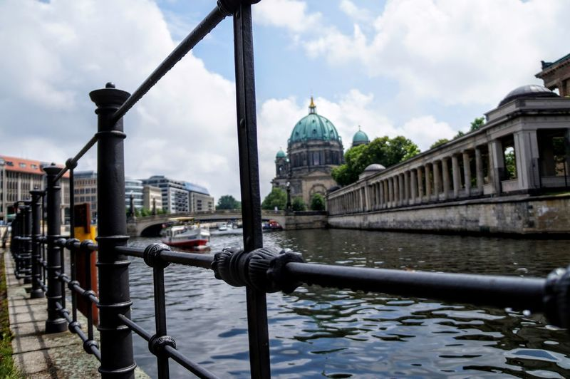 Berlin cathedral by river seen through railing in city