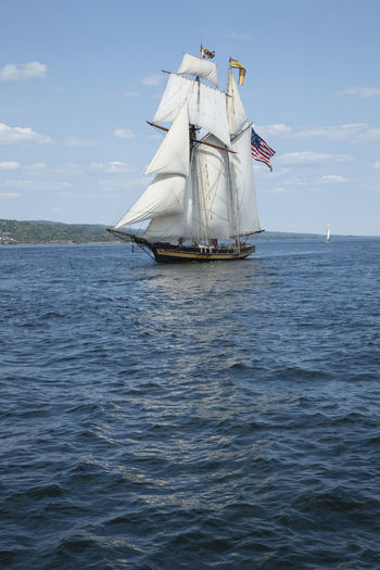 Sailing ship with american flag on sea against sky