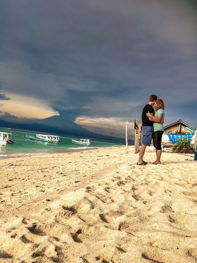 Full length of couple embracing at beach against sky
