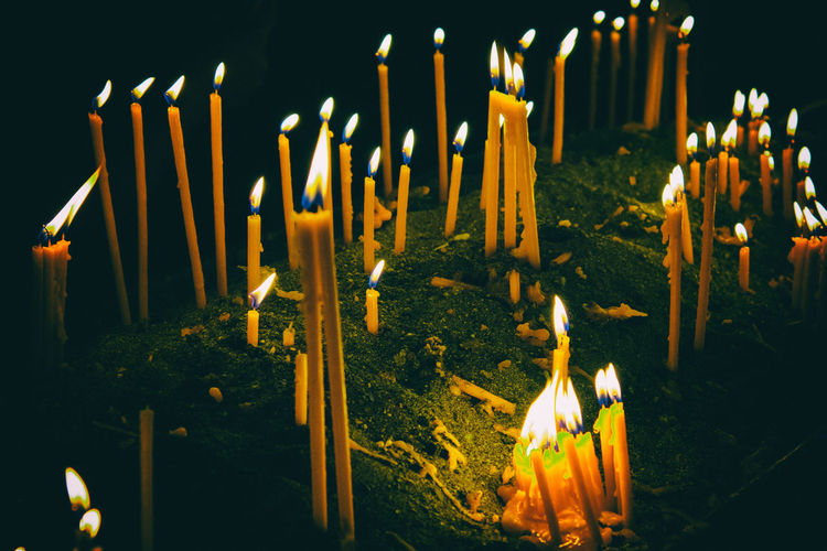 Close-up of lit candles at night