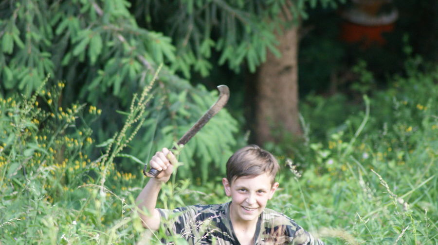Portrait of boy smiling while holding knife amidst plants