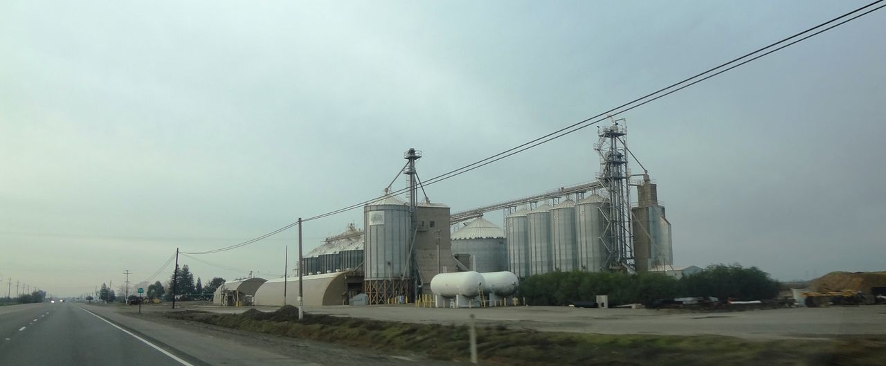Grain silo on the highway Day Electricity Pylon Farm Farm Life Grain Silos Industry No People Outdoors Sky