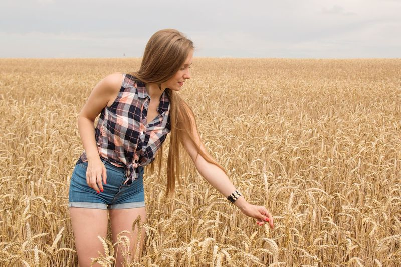 Full length of young woman standing in wheat field against sky