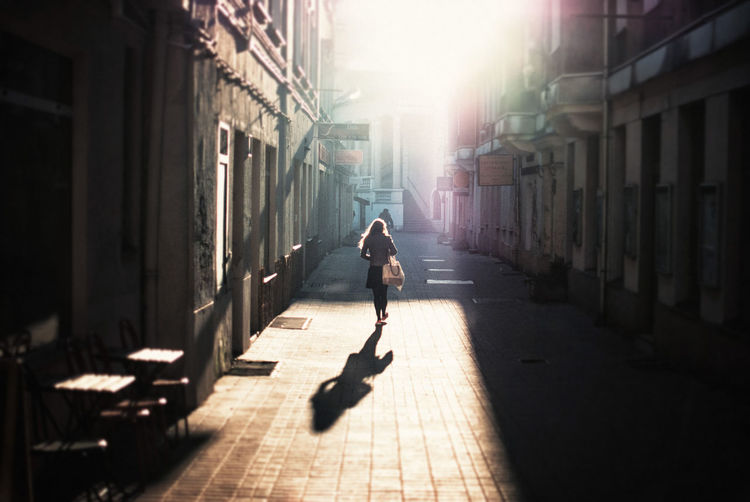 Rear view of woman walking on footpath amidst buildings during sunny day