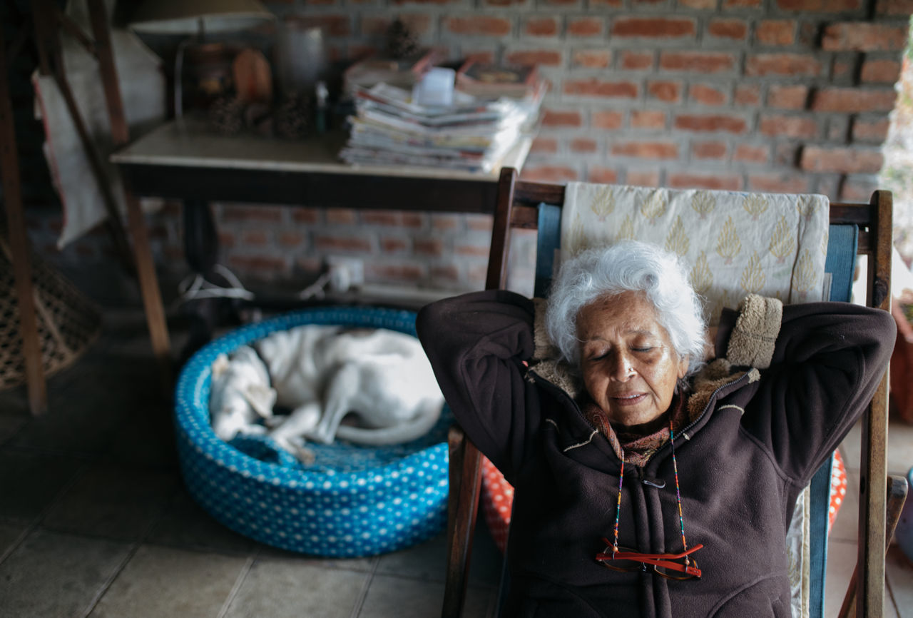 High Angle View Of Senior Woman Relaxing On Chair At Home