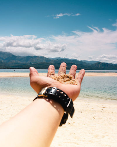 Low section of hand on beach against sky