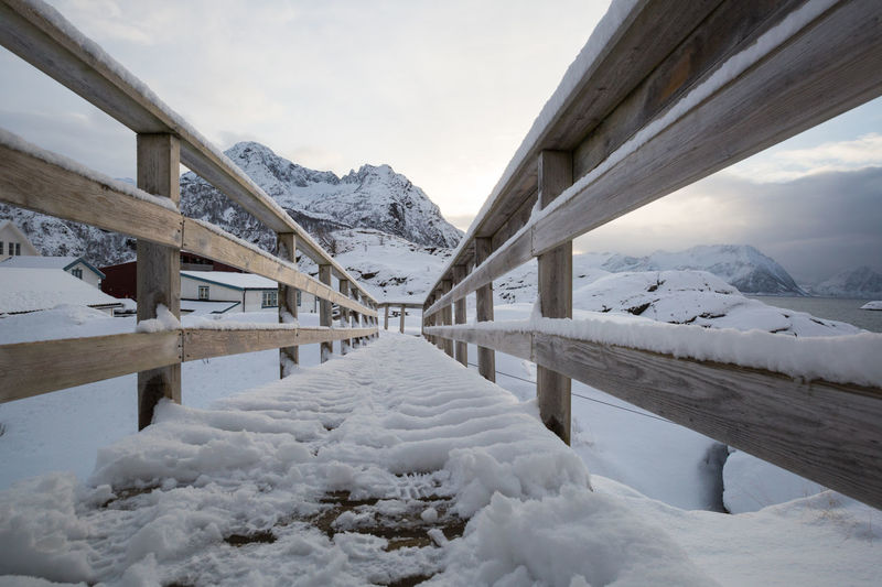 Low angle view of snow-covered footbridge Arctic Beauty In Nature Cold Temperature Connection Day Diminishing Perspective Dramatic Sky Dusk Footbridge Footpath FootPrint Idyllic Landscape Light - Natural Phenomenon Mountain Nature Outdoors Polar Climate Remote Scenics Snow Snowcapped Mountain Sunset The Way Forward Winter