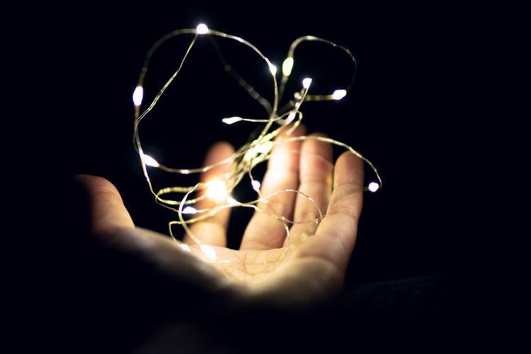 Close-up of hand holding illuminated light over black background