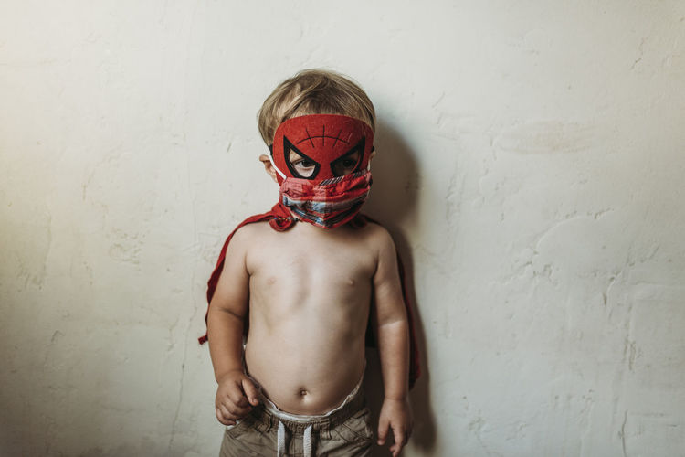 Midsection of shirtless boy standing against wall