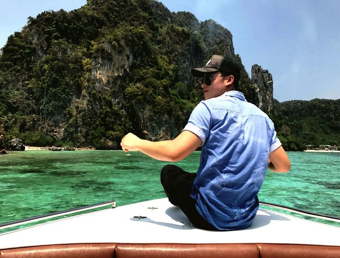 Rear View Of Young Man Sitting On Boat In Lake Against Cliff
