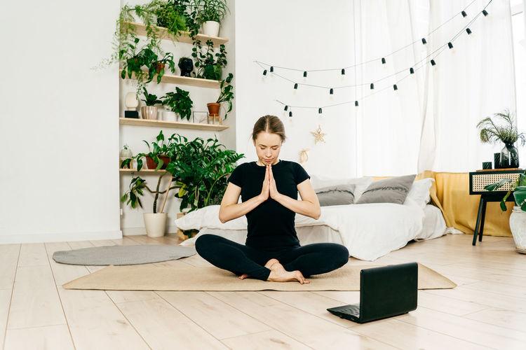 Full length of woman meditating at home