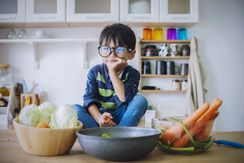 boy; cooking; food; cute; cook; chef; happy; fun; cheerful; funny; thinking; childhood; culinary; idea; happiness; concept; eating; thoughtful; delicious; preparation; nutrition; fastfood; dinner; expression; atmosphere; health; invent; joy; creative; vitamin; surprised; nutrient; serious; entertainment; recipe; friendly; little chefs; kitchen table; satisfied; chef cooking; mealtime; joyful; catering; household; lunch; gourmet; courses; advertising; ideas; process; charismatic; youngster Child One Person Childhood Lifestyles Casual Clothing Boys Real People Indoors  Food Eyeglasses  Males  Bowl Glasses Men Food And Drink Domestic Room Front View Sitting Innocence