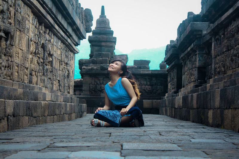 Full length of woman sitting against temple