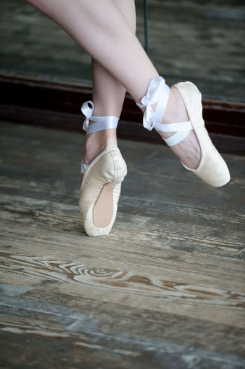Low Section Of Woman Wearing Ballet Shoe On Wooden Floor