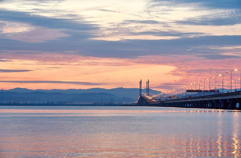 Illuminated bridge over lake against cloudy sky during sunset