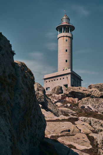 Low angle view of lighthouse amidst buildings against sky