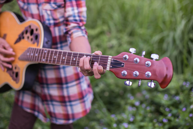 Midsection of man playing guitar in park
