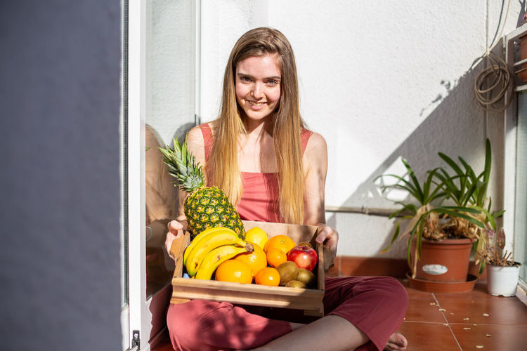 Portrait of young woman holding fruits