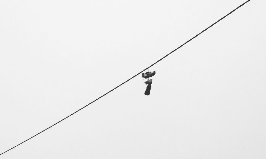 Low angle view of shoes on cable