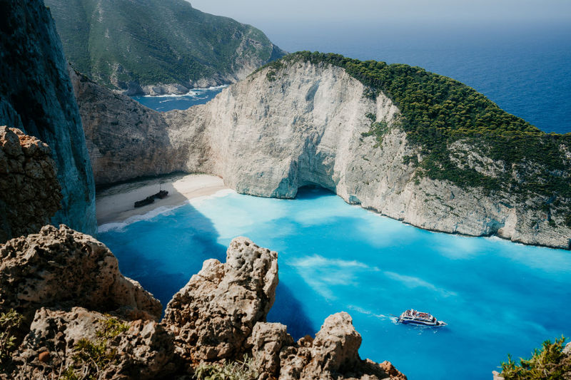 Navagio beach or Shipwreck bay with turquoise water and pebble white beach. Famous landmark location. Landscape of Zakynthos island, Greece Navagio Beach Zante Beauty In Nature Cliff Cove Day Environment High Angle View Lagoon Land Mountain Nature No People Non-urban Scene Outdoors Rock Rock - Object Scenics - Nature Sea Solid Tranquil Scene Tranquility Travel Destinations Turquoise Colored Water