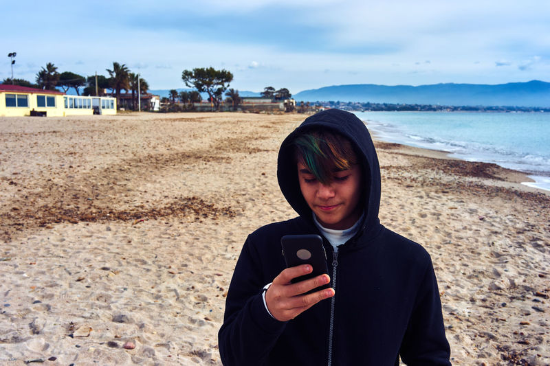 Young Man Using Phone While Standing At Beach