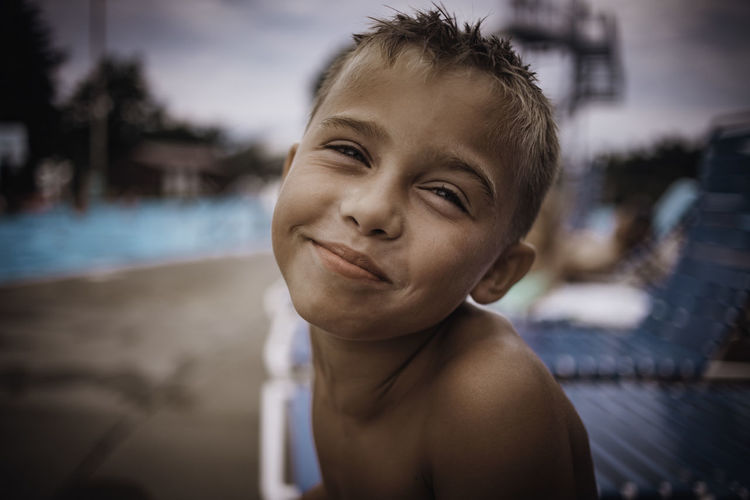 Close-up portrait of shirtless boy at poolside