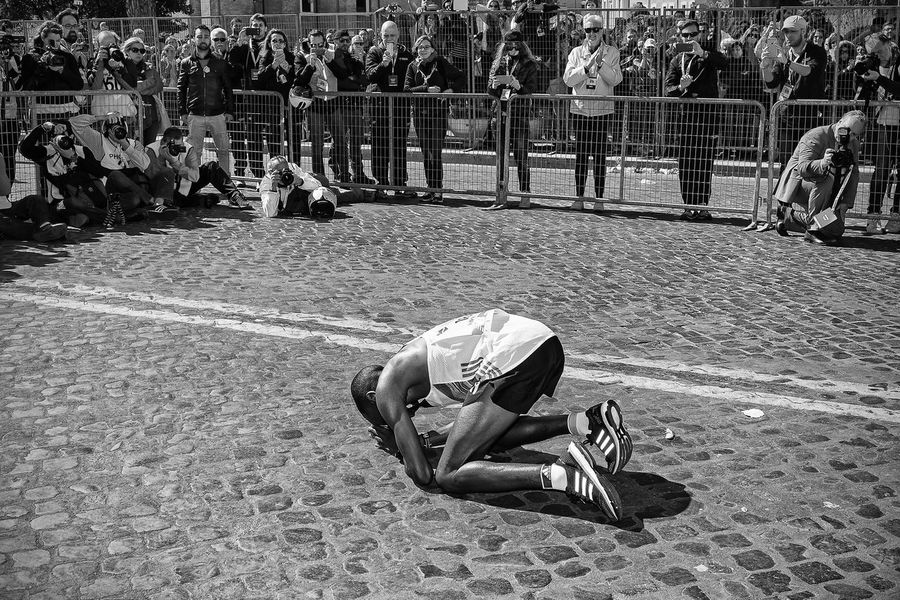 Rome, Italy - April 10, 2016: Amos Kipruto immediately after the line in Via dei Fori Imperiali kneels before the public and photographers and kiss the asphalt in gratitude for the achieved results. 2016 Amos Athlete Blackandwhite Gratitude Happiness Joy Kipruto Marathon Rome Victory Winner