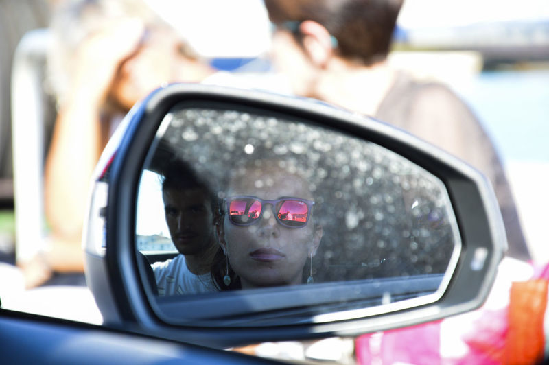 Reflection Of Couple In Car Side-View Mirror