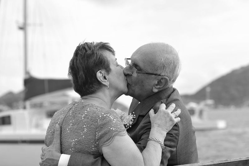 Close-Up Of Senior Couple Kissing While Standing Against Sky