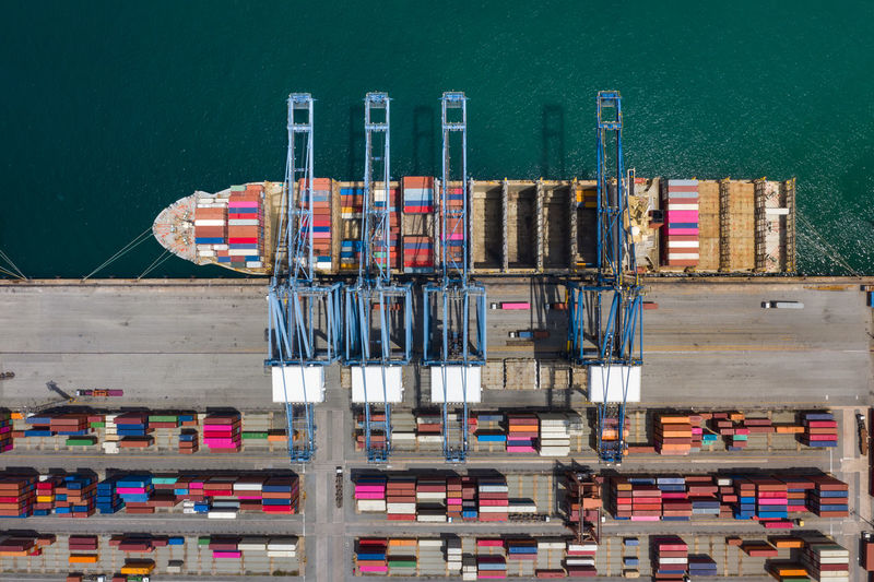 High angle view of commercial dock and containers ship loading on pier