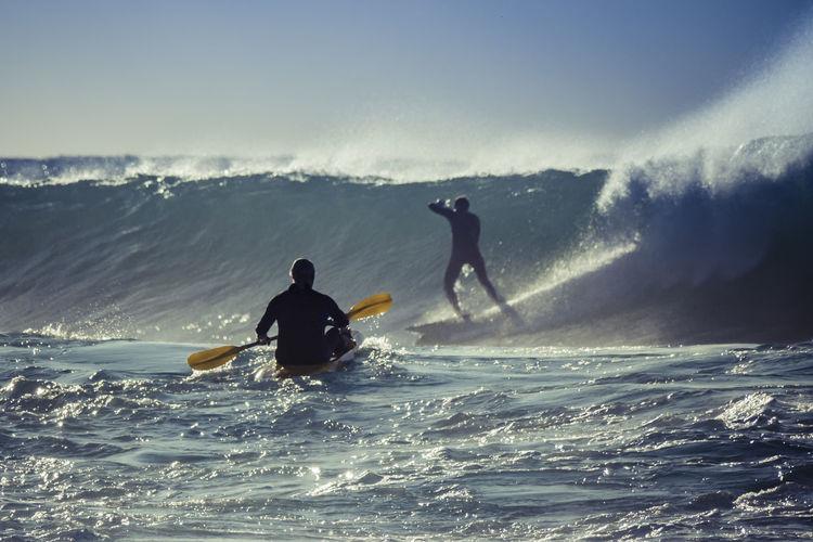 Friends surfboarding in sea against clear sky