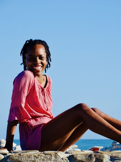 Portrait of smiling woman sitting at beach against clear blue sky