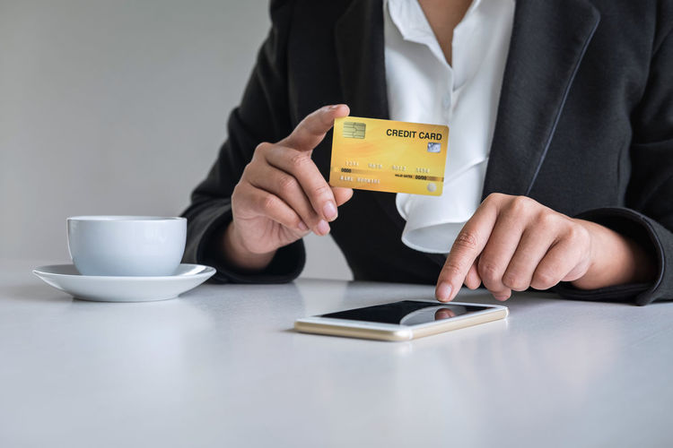 Midsection of woman using smart phone while holding credit card on table