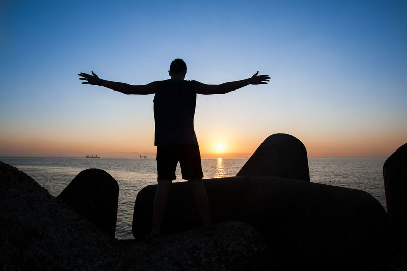 Silhouette man with arms outstretched standing on rock against sea during sunset