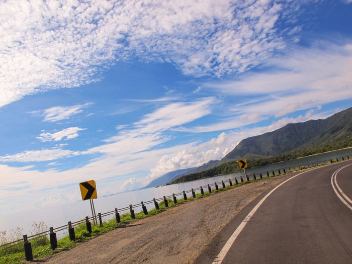 Driving Ocean Side Roads Beauty In Nature Cloud - Sky Day Direction Empty Road Environment Mountain No People Ocean Ocean Road On The Road Outdoors Road Road Sign Sign Sky Symbol The Way Forward Transportation