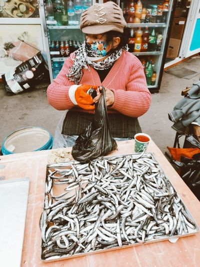 Woman holding fish for sale at market