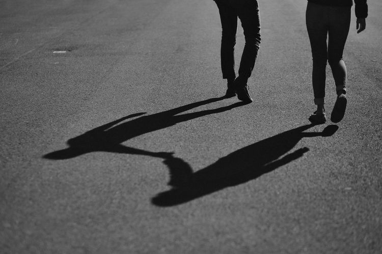 Low section of couple walking on road