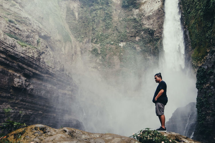 Full length of man standing on waterfall