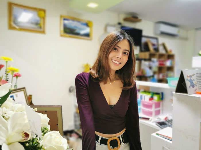 Portrait of smiling young woman standing in store