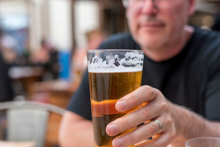 Midsection of man drinking beer glass