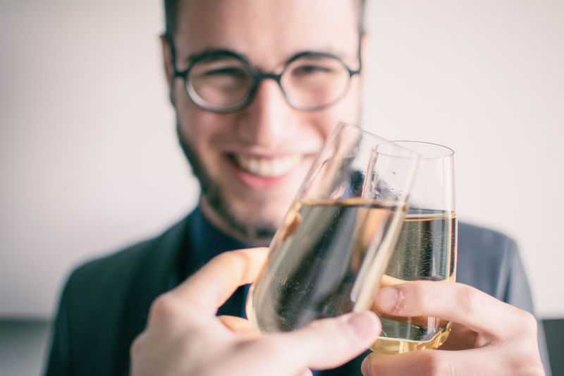 Champagne Cheers Close-up Day Drink Eyeglasses  Food And Drink Freshness Front View Holding Indoors  Leisure Activity One Person People Real People Smiling Young Adult