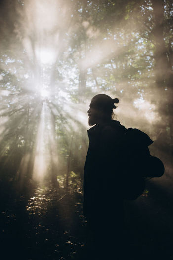 Silhouette woman standing by tree in forest