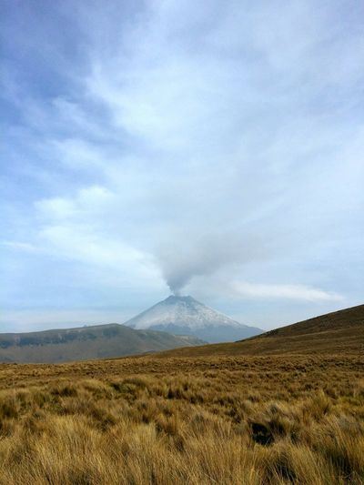 Scenic View Of Grassy Landscape And Active Volcano Against Cloudy Sky