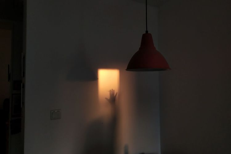 Silhouette person holding illuminated lamp at home