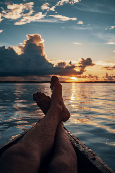 Amazonian sunset. Amazon Amazonas Rainforest Jungle South America Latin America Cloud - Sky Sunset Water Reflection Reflections In The Water Rippled Sun Boat Outdoors Nature Non-urban Scene One Person Real People Human Body Part Human Foot Men Personal Perspective Leisure Activity Adventure
