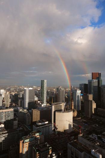 Rainbow over city buildings against sky