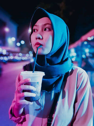 Young woman looking away while drinking coffee outdoors
