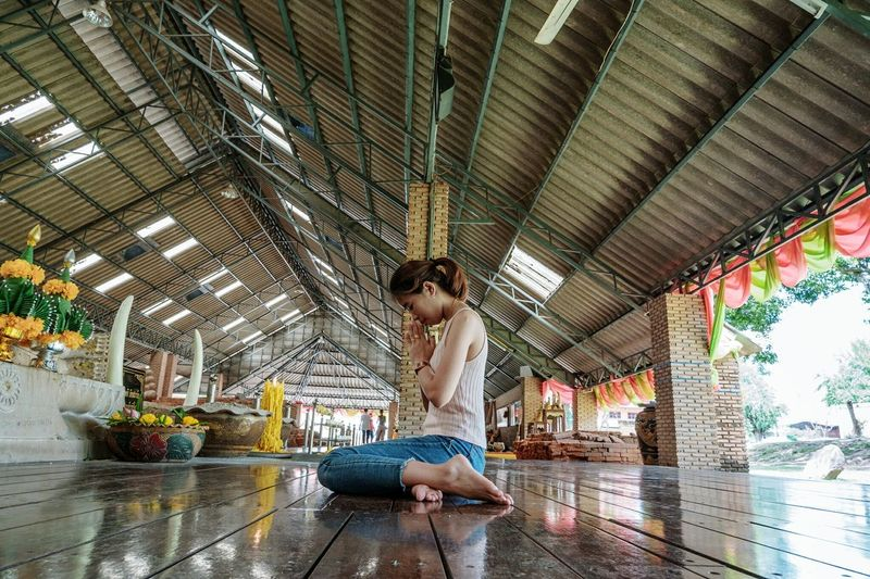 Full length of young woman sitting at temple